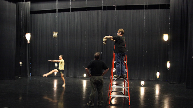 Eckwall works to hang the 38 fish skin lanterns in the Nancy Smith Fichter Dance Theatre.