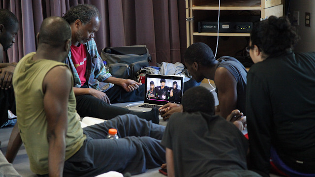 Reggie Wilson watches video with Fist and Heel Performance Group