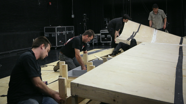The production crew re-assembles the ramp.